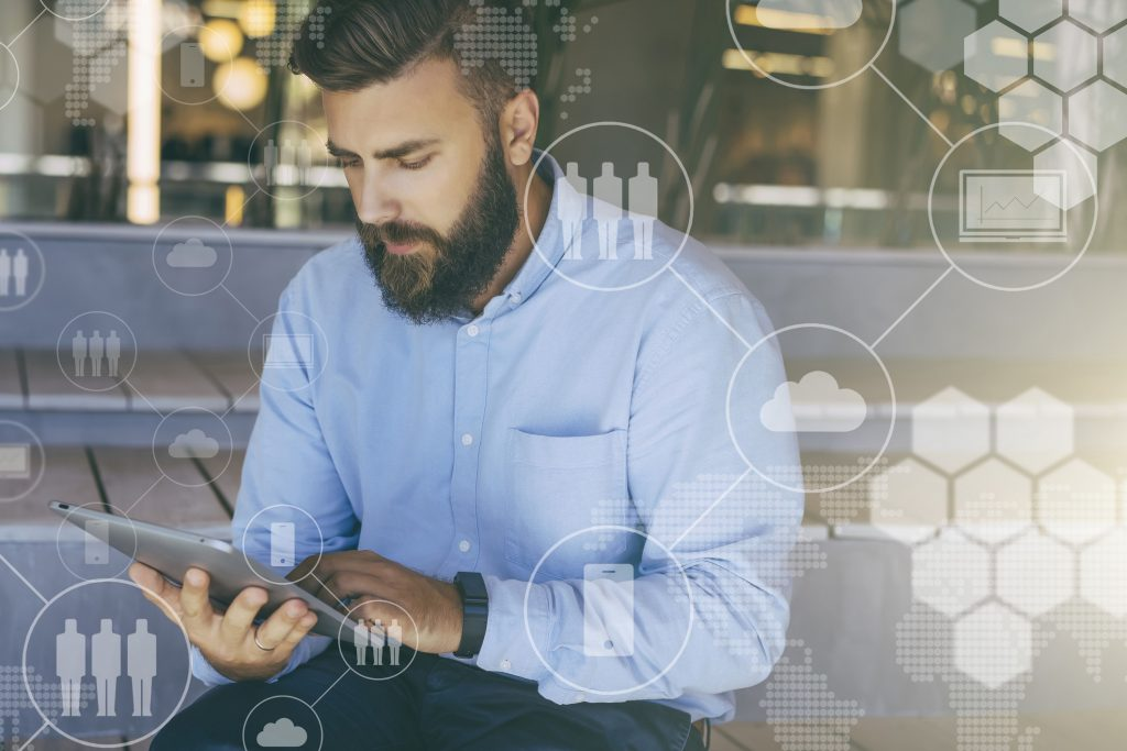 Young bearded hipster man sits and uses digital tablet. In foreground are virtual icons with people, clouds, digital gadgets. Guy blogging, chatting, working online. Social media. Lifestyle.